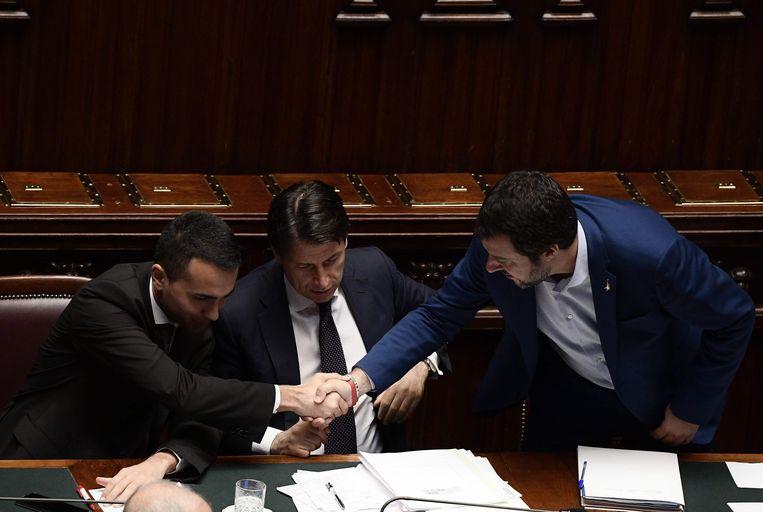 De Italiaanse premier Giuseppe Conte te midden van Luigi Di Maio (l) van de Vijfsterrenbeweging en Matteo Salvini (r) van de Lega in juni bij de stemming over het regeerakkoord. Beeld AFP