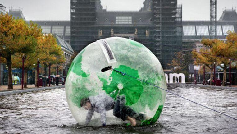 Hard gelachen werd er bij de vijver op het plein, waar geïnteresseerden in een grote doorzichtige plastic bal konden kruipen - met afdruk van de aarde erop - om te proberen in die bal over het water te lopen. Het idee: geef de aarde een duw in de goede richting. Foto Jean-Pierre Jans Beeld