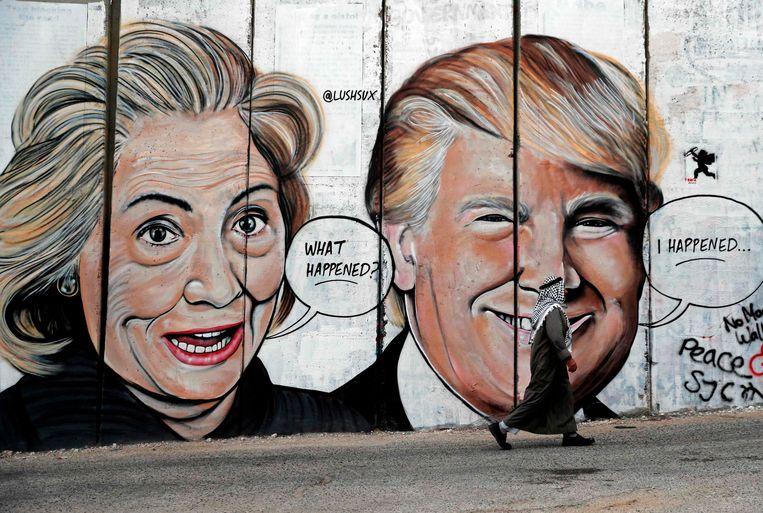 Een man in Palestina wandelt langs een muur met graffitiportretten van de Amerikaanse presidentskandidaten Hillary Clinton en Donald Trump. Beeld AFP