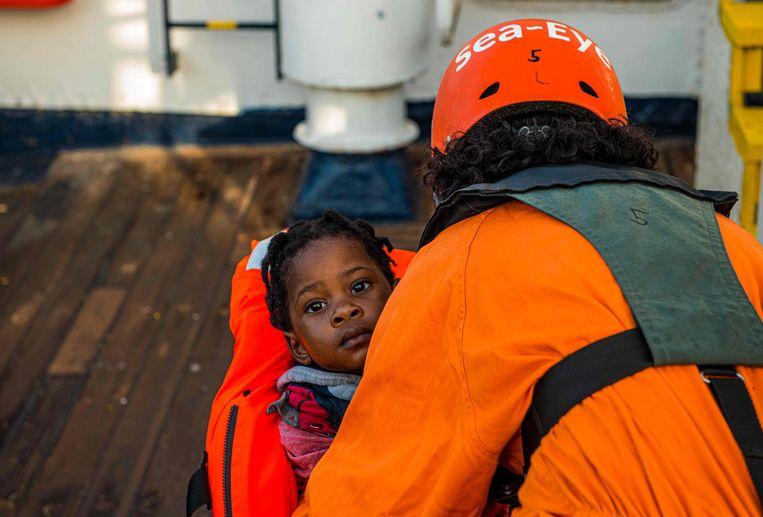 Een hulpverlener van Sea-Eye tilt een kind aan boord van het reddingsschip Alan Kurdi. Het meisje maakt deel uit van een groep van 40 migranten die woensdag werden opgepikt uit de wateren voor Libië. Beeld AFP