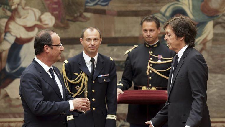 De Franse president Hollande (l) overhandigt Paul McCartney de onderscheiding. Beeld reuters