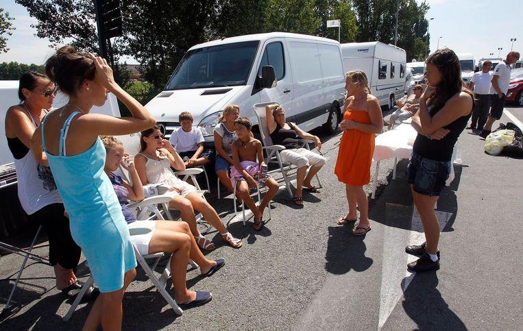 Een familie zit naast hun kampeerauto's in Bordeaux, Zuidwest-Frankrijk, 17 augustus 2010. Beeld Reuters