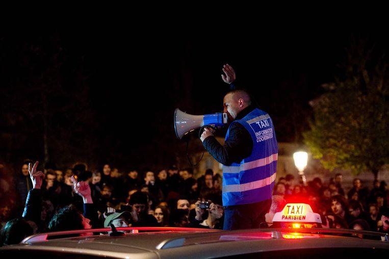 Een taxichauffeur spreekt door een megafoon tijdens een Nuit Debout. Beeld afp