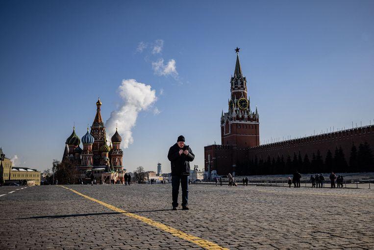 Een man gebruikt zijn mobiele telefoon op het Rode Plein in Moskou. Het Kremlin heeft Twitter een maand de tijd gegeven om 'extremistische berichten' te verwijderen. Beeld AFP