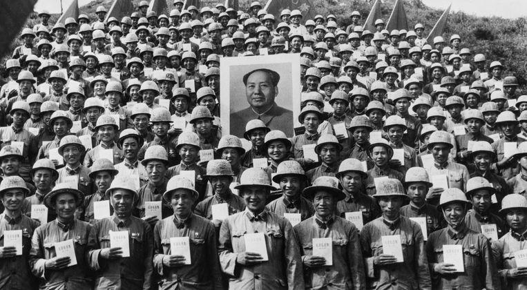 Soldaten van het Volksbevrijdingsleger poseren bij een portret van Mao met zijn Rode Boekje, december 1967. Beeld Getty