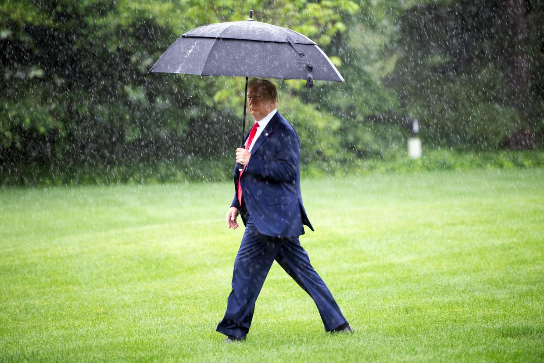 Donald Trump donderdag op het gazon van het Witte Huis op weg naar de presidentiële helikopter voor een trip naar Texas en New Jersey. Beeld AFP
