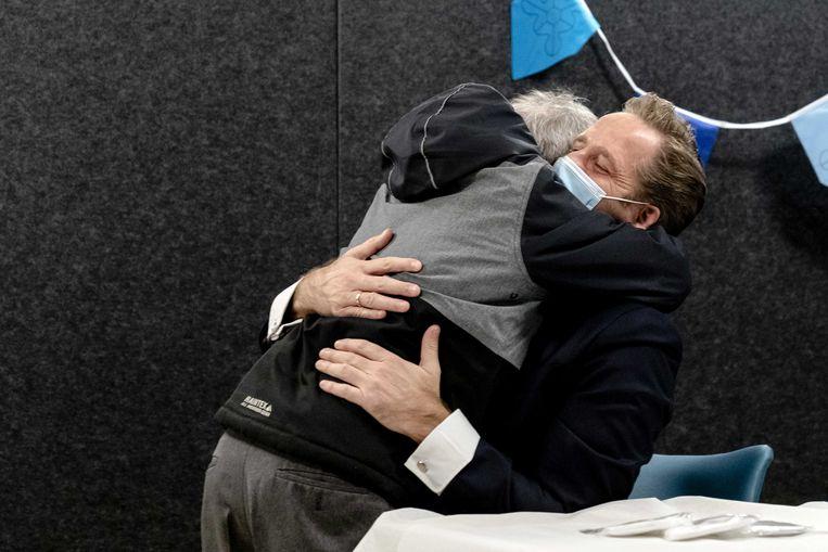 Demissionair minister Hugo de Jonge (Volksgezondheid) krijgt spontaan een knuffel van een van de bewoners, tijdens zijn bezoek aan zorginstelling 's Heeren-Loo in Monster. Na de eerste vaccinaties voor zorgmedewerkers is ook de vaccinatie van bewoners van verpleeghuizen en instellingen voor gehandicaptenzorg gestart. Beeld ANP
