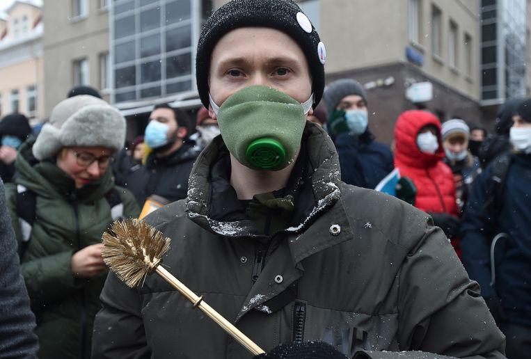Een demonstrant in Moskou houdt op 31 januari 2021 een gouden wc-borstel vast, het symbool voor de corruptie in Rusland. Beeld Reuters
