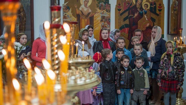 Oekraïense kinderen wachten op de mis in een orthodoxe kerk in de stad Slavjansk. Ook het Orthodoxe Pasen wordt dit weekeinde gevierd. Beeld EPA