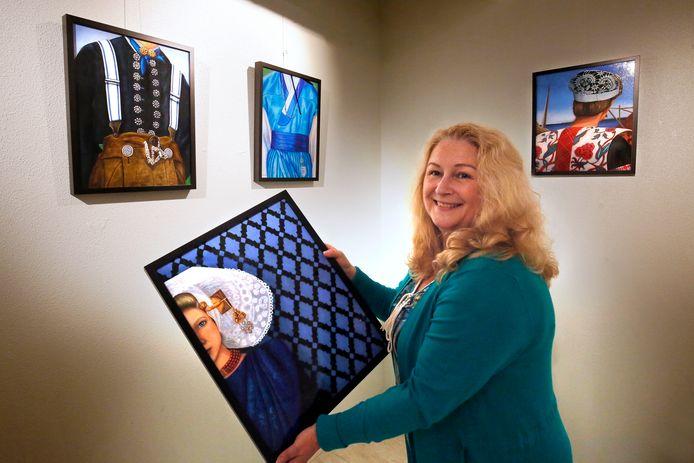 Gorcumse fijnschilder Cordula van der Stadt richt haar expositie in. In haar handen heeft ze een portret van een Zeeuwse in klederdracht.