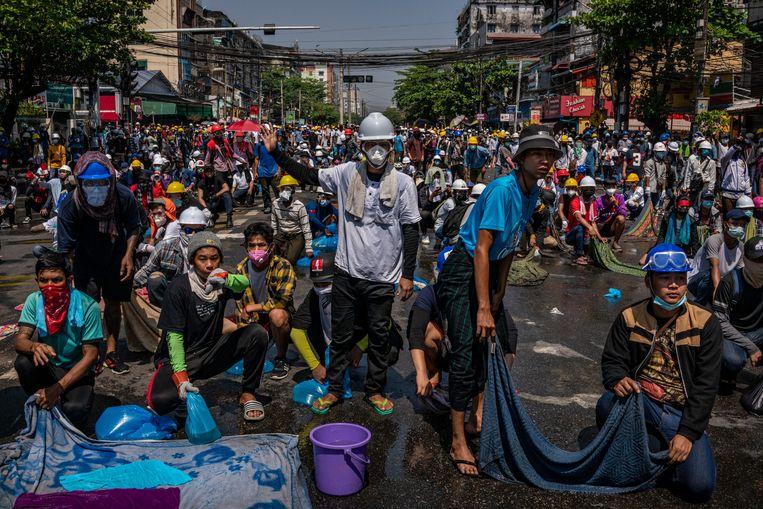 Demonstranten in Yangon staan klaar met doorweekte lakens om te gebruiken tegen het traangas van de politie. Beeld Getty Images
