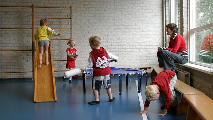 Kinderen en juf in gymzaal.