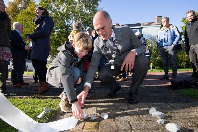Loco-burgemeester Kees van Dalen legt samen met een jonge bezoeker de struikelsteen voor Levie Mozes.
