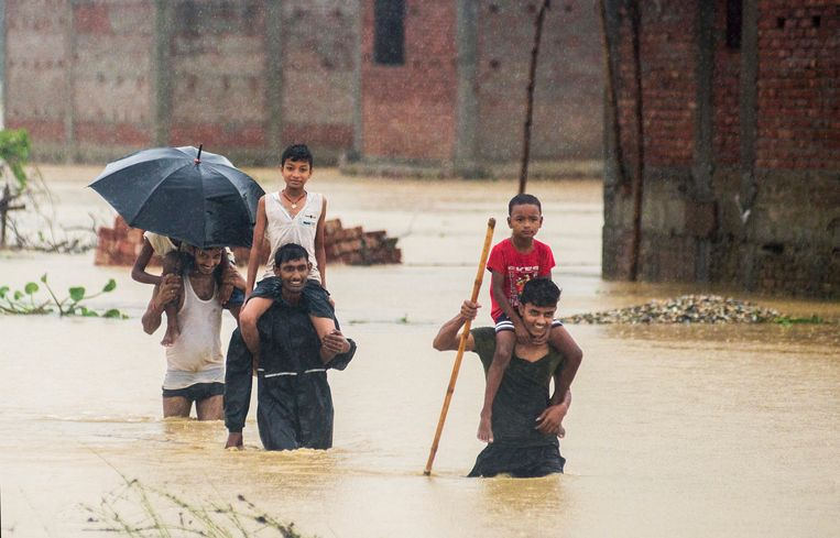Nepalese men carry children on their shoulders as they wade through flood waters in village Ramgadhwa in Birgunj, Nepal, Sunday, Aug. 13, 2017. An official said torrential rain, landslides and flooding have killed dozens of people in Nepal over the past three days, washing away hundreds of homes and damaging roads and bridges across the Himalayan country. (AP Photo/Manish Paudel) Beeld AP
