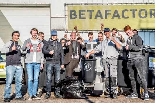 Professor Martin Seijffers (l) en broer John (r) naast afvalrobot Urby, met de studenten van TU Delft.