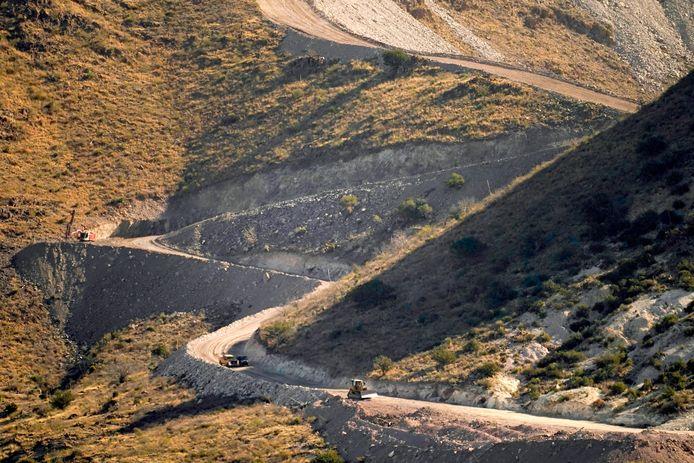 Arbeiders bereidden de constructie van de grensmuur voor met explosies in Arizona. Rechts ligt Mexico, links de Verenigde Staten. Smokkelaars maken nu dankbaar gebruik van de aangelegde werkwegen.