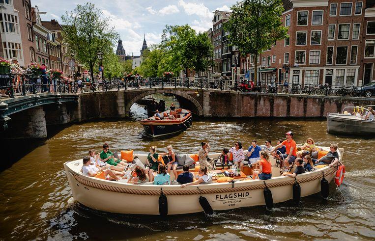Bootjes op een gracht in het centrum van Amsterdam, op de eerste landelijke tropische dag van 2019.  Beeld Robin van Lonkhuijsen / ANP
