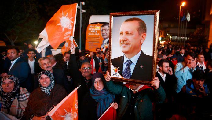 Mensen houden een portret van de Turkse president Tayyip Erodgan vast buiten bij het hoofdkwartier van de AP-partij.