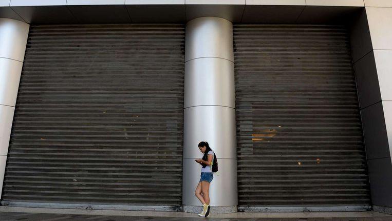 Een vrouw komt aan bij een gesloten deur bij een winkelcentrum in Caracas. Ook winkelcentra zijn gesloten om energie te besparen. Beeld afp