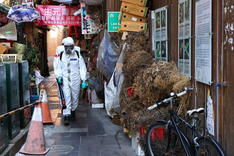 Militairen desinfecteren de uitgaanswijk Wanhua in de hoofdstad Taipei (Taiwan).  Beeld Reuters
