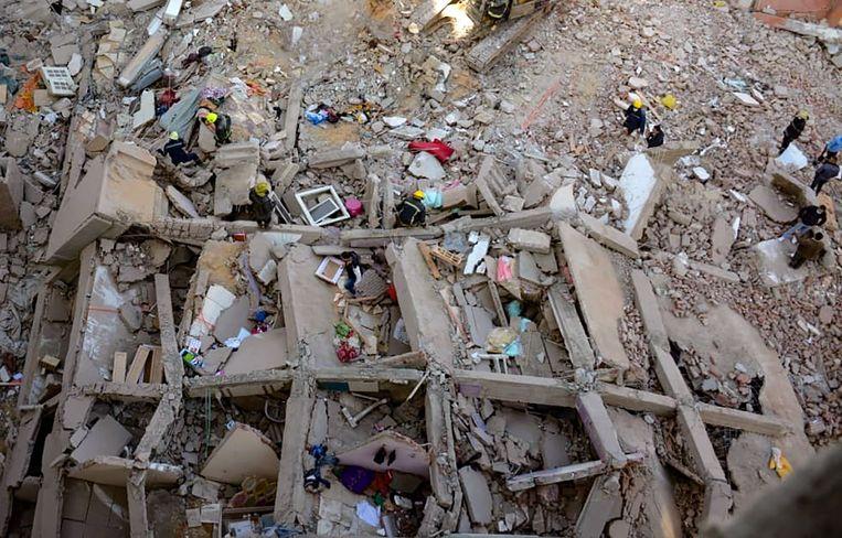 Reddingswerkers in het puin van het ingestorte gebouw.  Beeld AFP