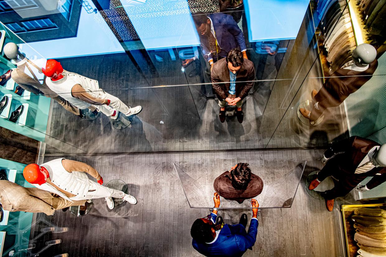 Bij Suitsupply wordt wél coronaproof gewerkt: grote plexiglas-kamerschermen waar de verkoper zijn handen doorheen steekt. Beeld Hollandse Hoogte / Robin Utrecht