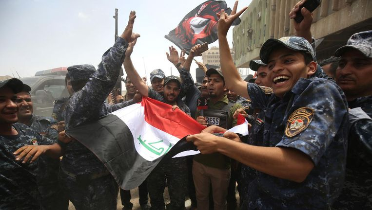 Iraakse militairen en agenten vieren de overwinning op IS in Mosul. Beeld Ahmad Al-Rubaye / AFP