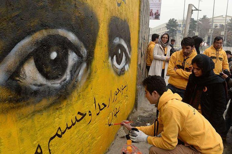 Afghaanse straatartiesten maken een muurschildering voor Internationale Vrouwendag. Beeld null