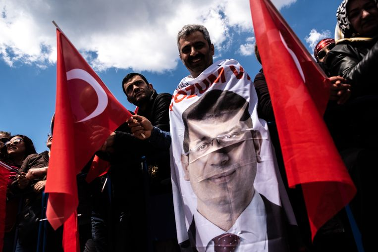 CHP-aanhangers zwaaien op zondag 21 april een vlag met het portret erop van Ekrem Imamoglu, hun hoop in bange dagen. Beeld Joris van Gennep