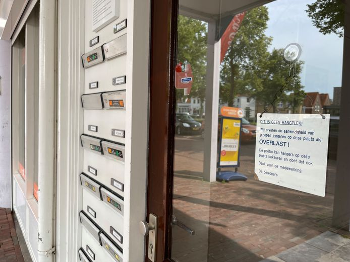 Bij de voordeur van portiekwoningen boven winkels aan de Beenhouwerssingel in Middelburg hangt een bordje dat waarschuwt tegen overlast.