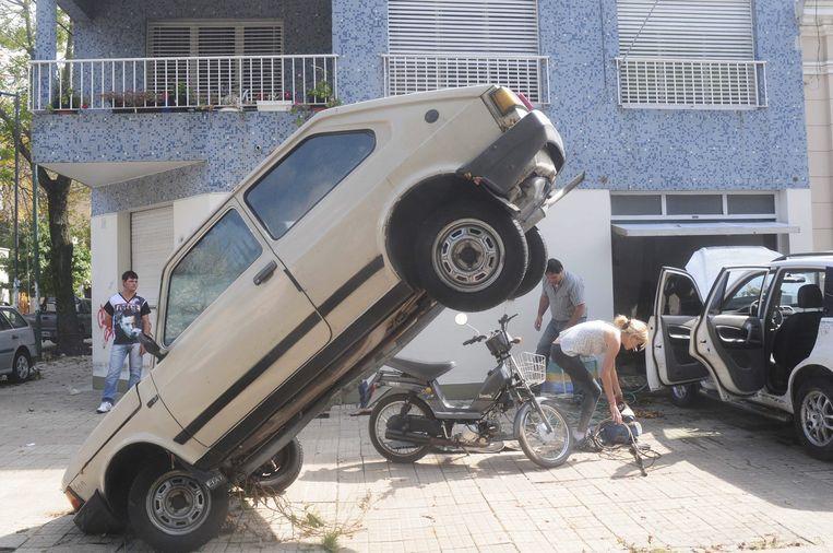 Een auto hangt tegen een omgebogen paal nadat het water in de Argentijnse stad La Plata is gezakt. Beeld EPA