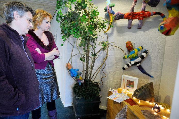 Schooldirecteur Hanneke Klerks links en moeder Elisa Hoogendoorn staan in 2011 stil bij het herdenkingsplekje voor Emiel, dat in de hal van basisschool Darwin werd ingericht.