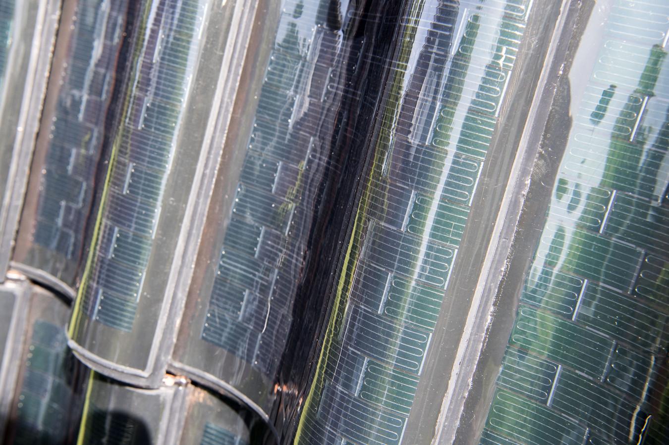De film van zonnecellen op een traditionele dakpan.