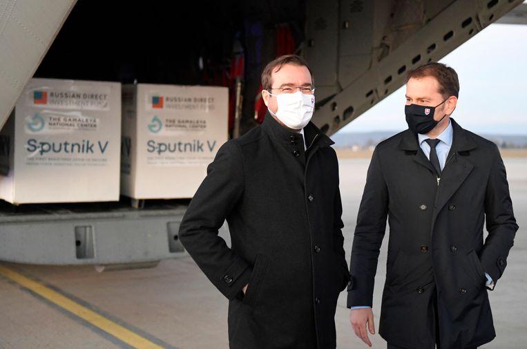 De Slowaakse premier Igor Matovič en Minister van Gezondheid Marek Krajci op een vliegveld in Košice, met op de achtergrond het Sputnik V-vaccin. Beeld AP