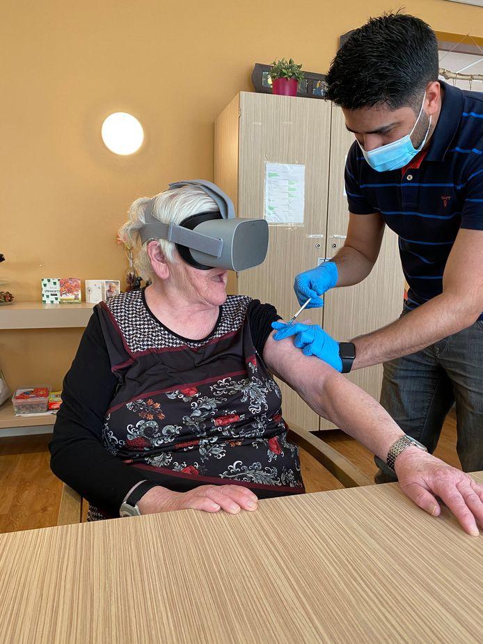 Een bewoonster van S&L Zorg, een woonzorgcentrum in Roosendaal voor mensen met een verstandelijke beperking, krijgt haar tweede vaccinatie met een V&R bril op.