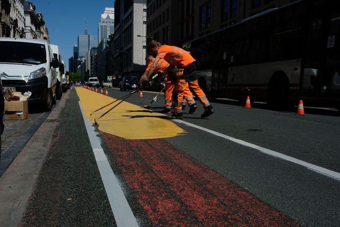 Arbeiders schilderen een fietspad op de Jacqmainlaan.
