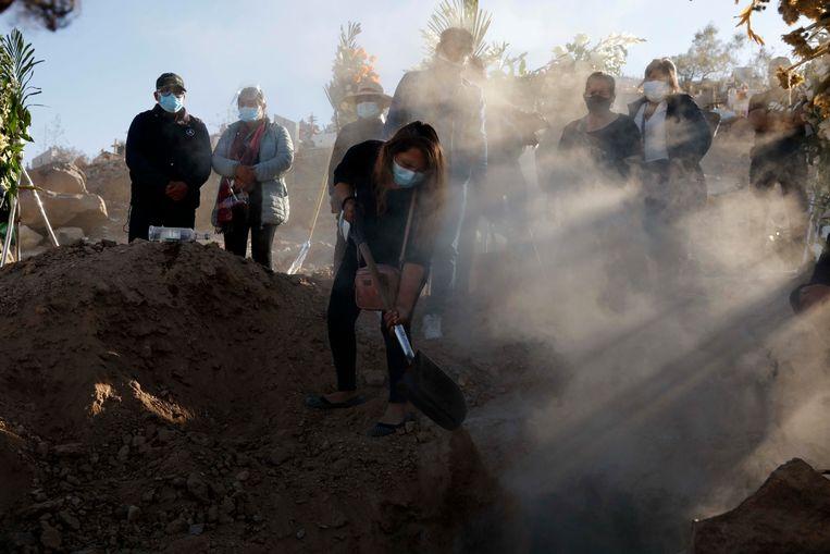Op een begraafplaats in Arequipa in Peru scheppen nabestaanden zand in het graf van een man die overleed aan Covid-19. In Peru wordt 90 procent van de besmettingen veroorzaakt door de lambdavariant. Beeld AP