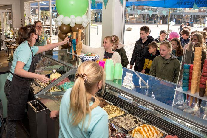 Xanna Everaers neemt het eerste ijsje in ontvangst in de gloedjenieuwe ijssalon van haar familie. moeder Tessa (tweede van links) kijkt toe