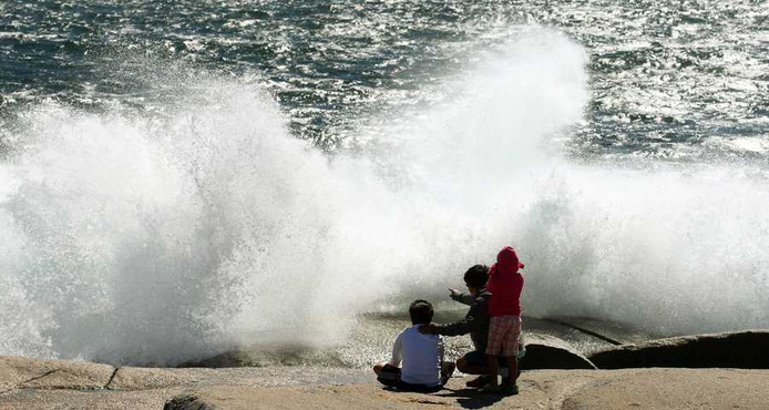 Toeschouwers bij de hoge golven, veroorzaakt door het staartje van orkaan Irene, maandag bij Peggy's Cove in Nova Scotia, Canada.