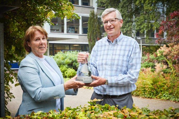Rector/bestuurder a.i. mevrouw D. Hoekstra en scheikundedocent Martin Groeneveld tonen de Erlenmeyer, de trofee die leerling Jochem van den Broek voor het Lorentz Casimir Lyceum in de wacht sleepte.