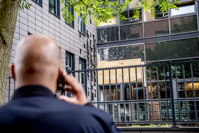 Een voorbijganger bekijkt de plek waar een kantoorpand is beschoten met een antitankwapen. In het pand zit onder meer Pijper Media. Dit is de uitgever van bladen als Panorama en Nieuwe Revu, die hier ook hun redacties hebben.