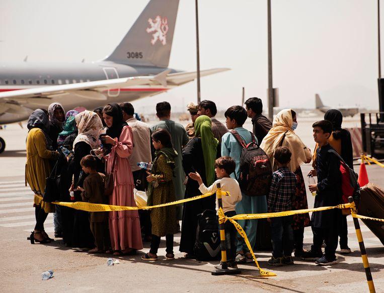 Afghanen houden zich klaar voor evacuatie op de luchthaven van Kaboel. Beeld AP