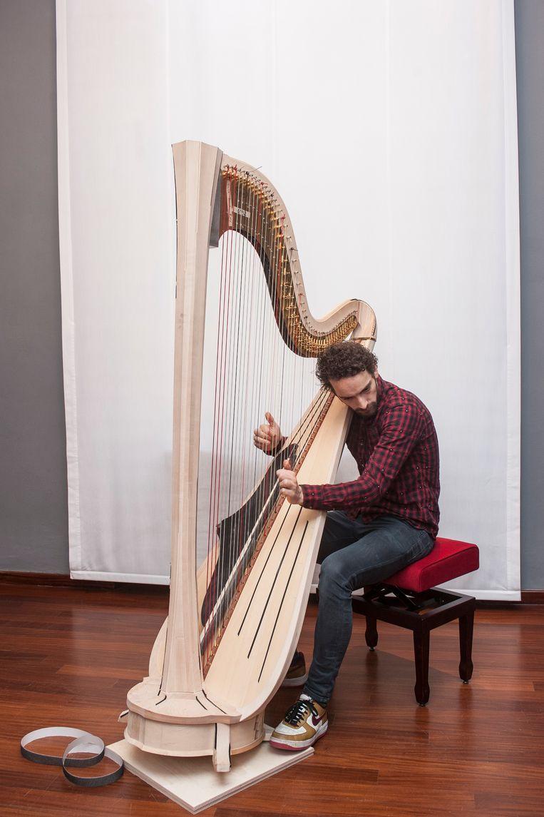 Remy van Kesteren met de harp, een strak blank instrument. Beeld Marta Giaccone