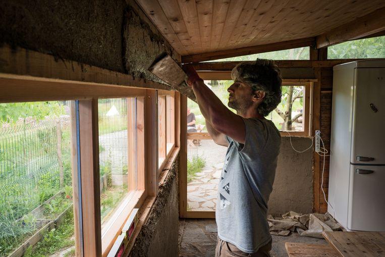 Xavier Allard is gespecialiseerd in het bouwen van woningen van aarde, stro en hout (foto links), zoals die van de familie Ertem. Beeld Nicola Zolin