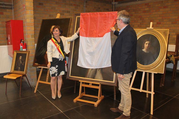 Burgemeester Irina De Knop (links) en Masiuskring-voorzitter Joris De Beul onthullen het nieuwe portret van Frans-Jozef De Gronckel.