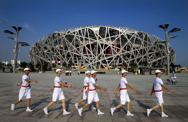 Vrijwilligers lopen op het plein voor het Olympisch stadion in Peking, in de volksmond het Vogelnest genoemd. Beeld null