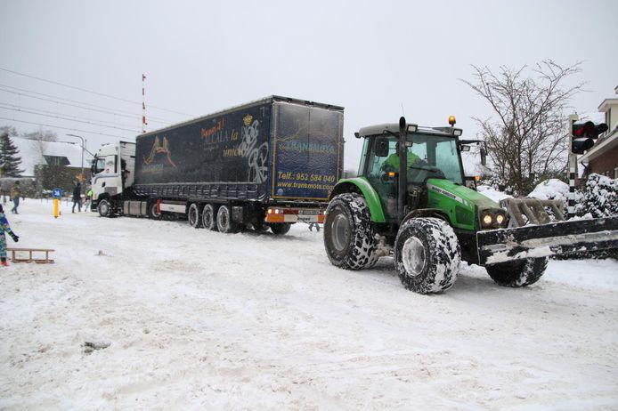 Een vrachtwagen is vast komen te zitten in de sneeuw op de spoorwegovergang bij de Groeneweg in Rheden.