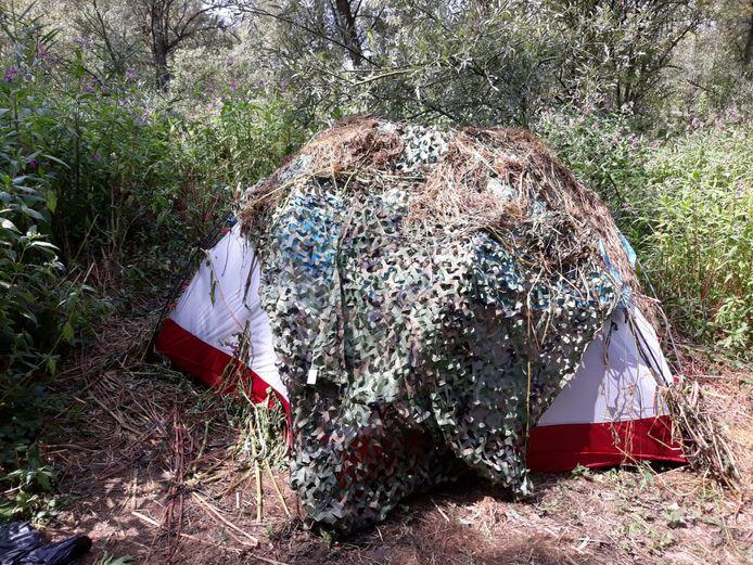 De tent stond verstopt onder een camouflagenet.