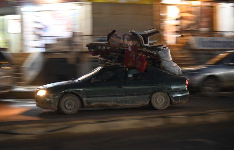 Syriërs rijden met hun eigendommen op het dak van een auto door Atme, nabij de Turkse grens.  Beeld AFP