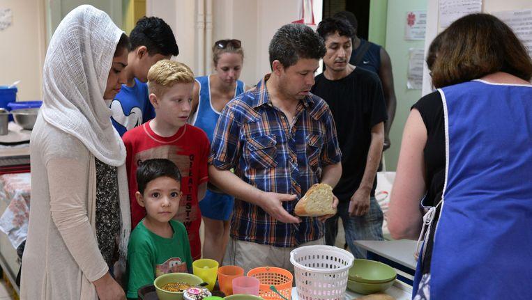Caritas deelt maaltijden uit aan vluchtelingen in Griekenland. Beeld GETTY